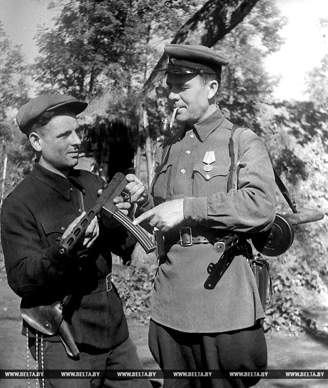 Партизанский оружейник - Яков Менкин (слева) передает сделанный им автомат командиру отряда имени Котовского Николаю Баранову. 1943 год