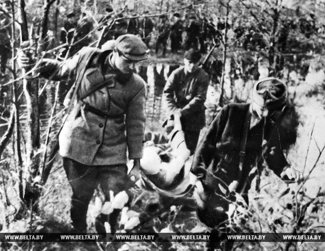 Партизаны бригады им. В.В. Куйбышева возвращаются с боевого задания с раненым товарищем. 1943 год