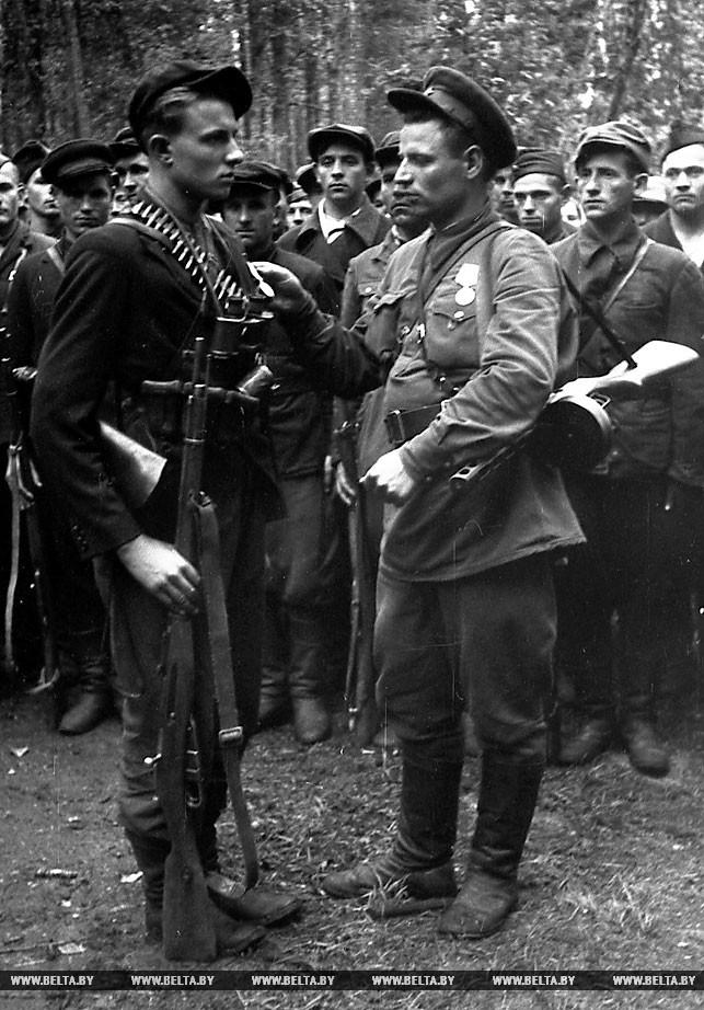 Комиссар партизанского отряда Ф.И.Лисович (справа) вручает медаль партизану-разведчику комсомольцу Николаю Кулакевичу. 1943 год
