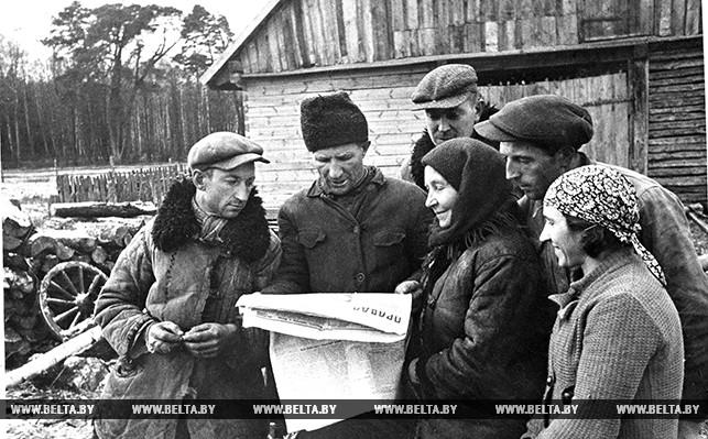 """Группа бывших батраков польской помещицы Бынской, получивших землю, скот и жилье, читают газету """"Правда"""""""