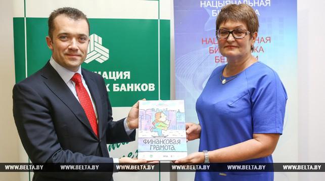 Региональный менеджер компании Visa в Беларуси и Молдове Игорь Ковалев вручает книгу заместителю директора Национальной библиотеки Беларуси Татьяне Кузьминич