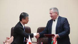 Хироки Токунага и директор территориального центра социального обслуживания населения Витебского района Леонид Ковалев подписывают грант-контракт