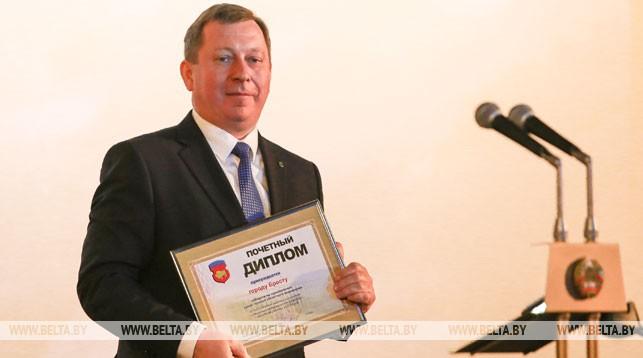 Председатель Брестского горисполкома Александр Рогачук держит диплом городу Бресту - победителю соревнований среди городов областного подчинения