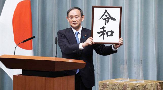 """Генеральный секретарь кабинета министров Ёсихидэ Суга демонстрирует табличку со словом """"Рэйва"""". Фото   AP Photo"""