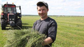 Механизатор Александр Ступень занят на подборке подвяленной травы и упаковке ее в полиэтиленовую пленку