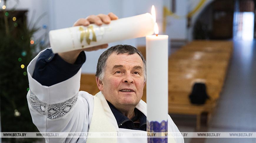 Ксендз Генрих Акалатович зажигает свечу от Вифлеемского огня мира