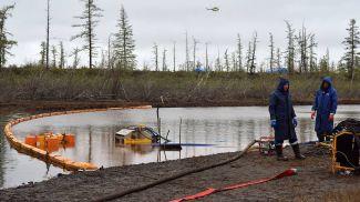 """Сотрудники специальной службы компании """"Транснефть-Сибирь"""" очищают реку Амбарную от последствий разлива топлива на ТЭЦ-3. Фото ТАСС"""
