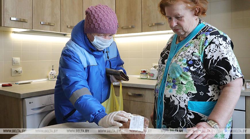 Соцработник Лидия Шайтор передает продукты жительнице Лепеля Галина Смальцер. Фото из архива