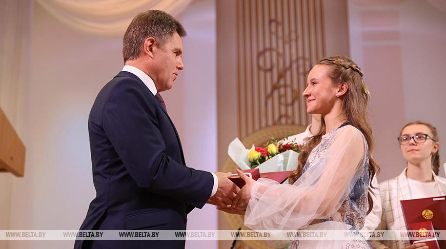 Игорь Петришенко вручает нагрудный знак Ангелине Ломакиной