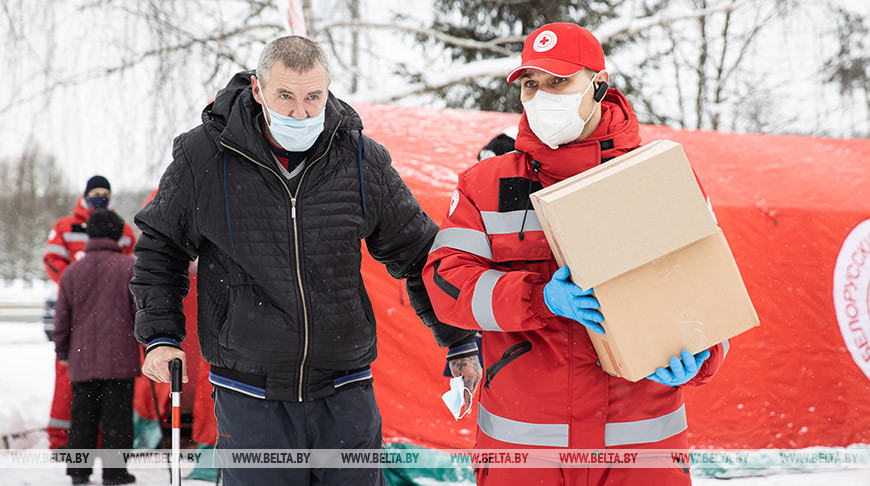 Главный специалист Минской городской организации БОКК Артем Арешко помогает отнести продуктовый и гигиенический набор