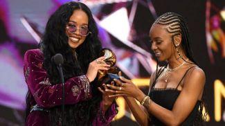Певица H.E.R (слева) получает статуэтку за лучшую песню года. Тиара Томас (справа) - одна из авторов победившей композиции. Фото Getty Images