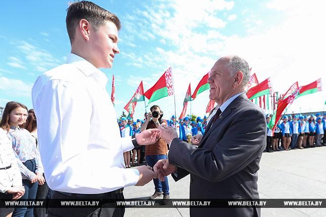 Председатель Совета Минской городской организации ветеранов Анатолий Адоньев вручаетчленские билеты БРСМ