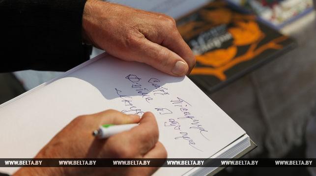 Писатель Михаил Бусько подписывает автограф своему читателю