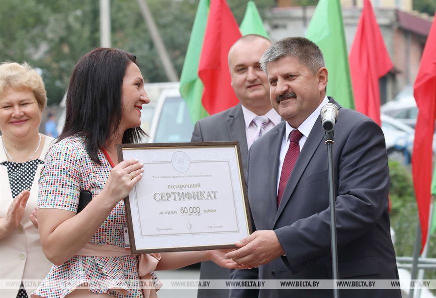Председатель Гомельского облисполкома Геннадий Соловей вручает подарочный сертификат директору центра Оксане Козаченко