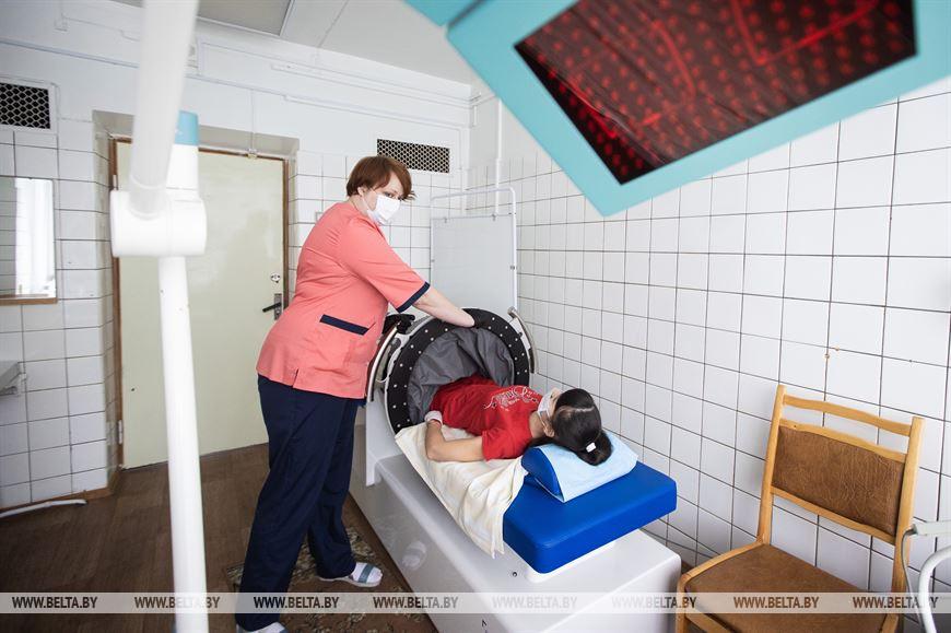 Медицинская сестра физиотерапевтического отделения Марина Макова включает аппарат для вакуумной терапии