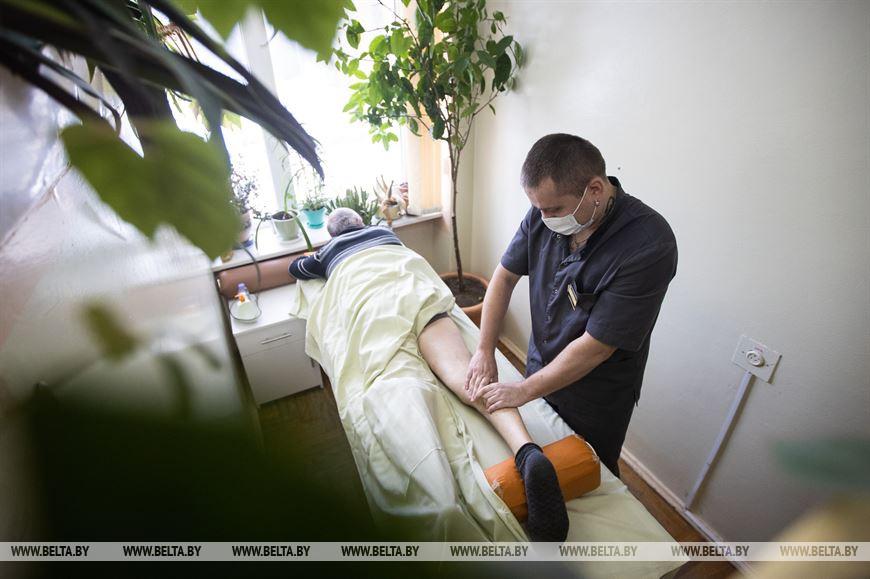 Массажист физиотерапевтического отделения Дмитрий Михайлович делает восстанавливающий массаж пациенту