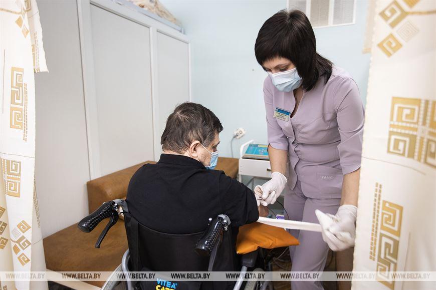 Медицинская сестра физиотерапевтического отделения подключает аппарат электростимуляции мышц пациенту Вадиму Ржевусскому